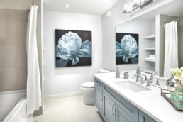 A large, mostly white, bathroom with baby blue accents. Modern bathroom featured in a brand new Kimberley Homes model, located in Jagare Ridge.